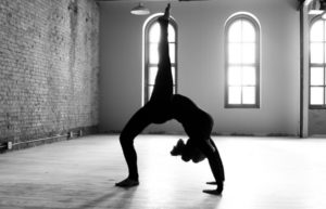 woman in upside-down yoga pose in black and white